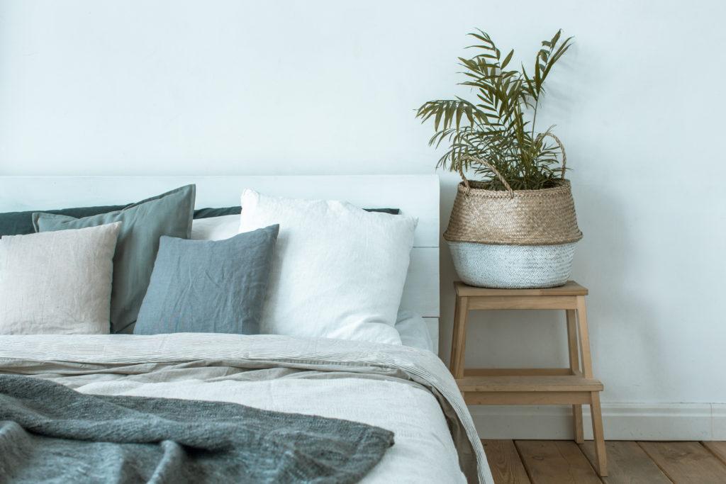 Einrichtung Ferienwohnung, Nachhaltigkeitssiegel, Bett mit Pflanze daneben