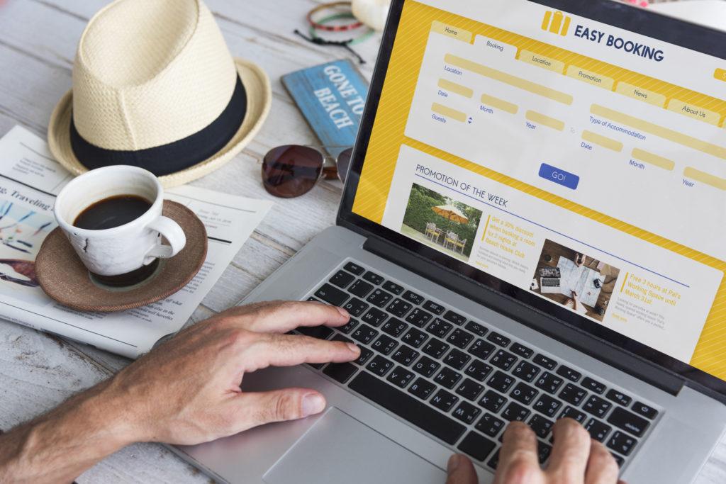 Online Buchungsplattform für Ferienwohnungen auf Laptop geöffnet, Sonnenhut und Kaffeee danebn