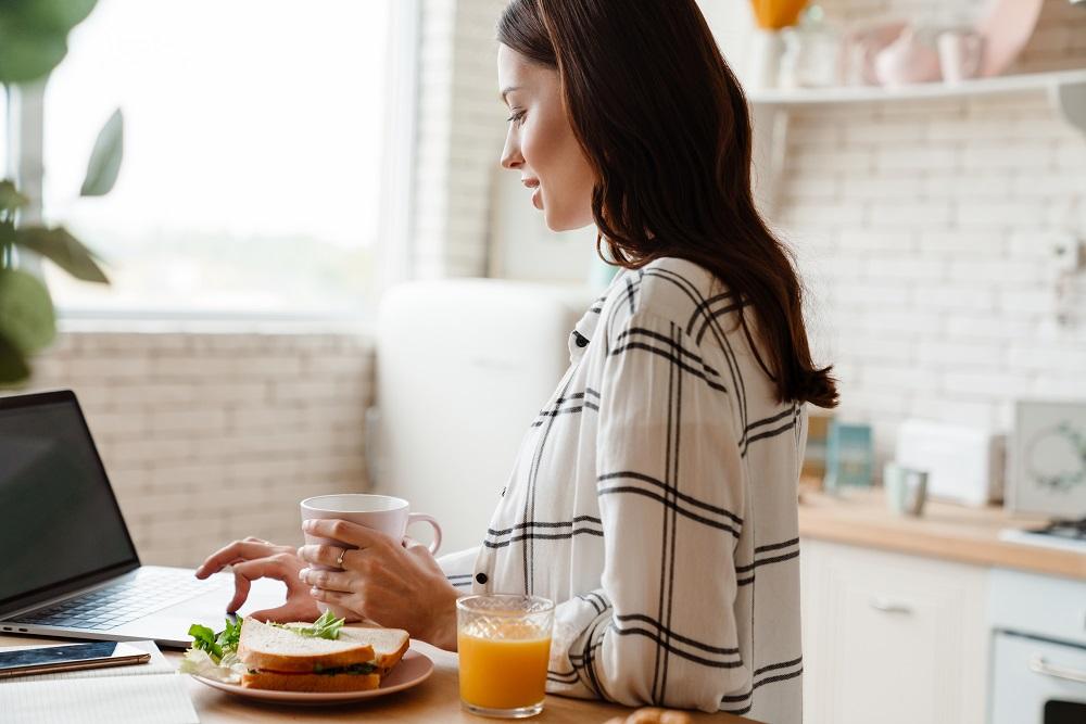 Ferienwohnung inserieren, Frau bei der Inserierung am Laptop in der Küche, Getränk und Snack