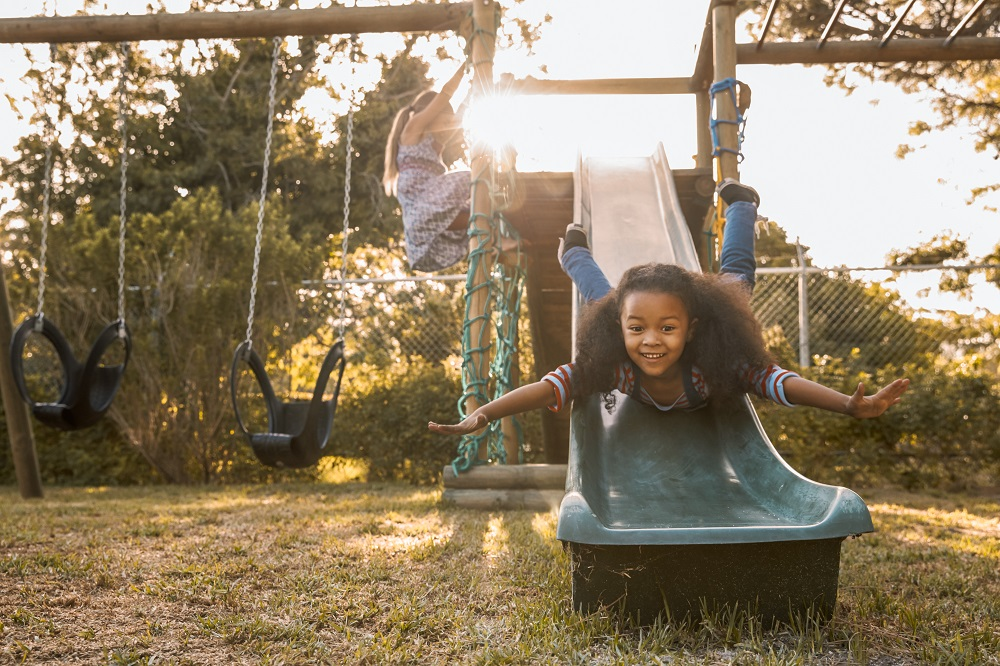 Spielmöglichkeiten Kinder Garten, Mädhcen auf Klettergerüst und Rutsche