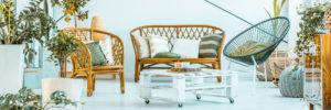 Wohnzimmer Ferienwohnung mit Korbmöbeln und weißem Tisch
