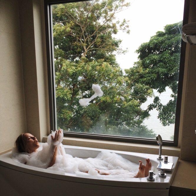 Badezimmer einer Ferienwohnung, Frau im Schaumbad