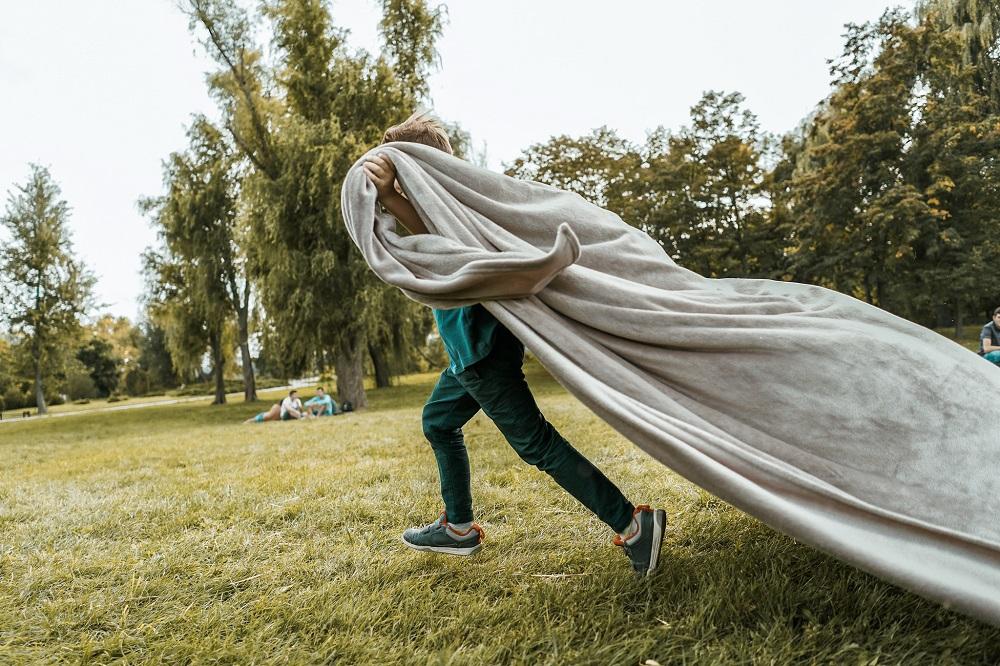Kind rennt durch Garten einer Ferienwohnung mit einer Decke
