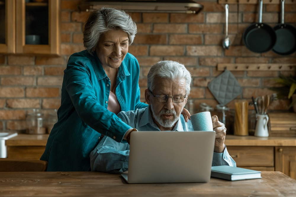 Ferienwohnung vermeiten, älteres Paar bei der Buchung vor dem Laptop