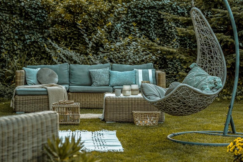 Gartenbereich der Ferienwohnung mit Korbmöbeln und Hängesessel
