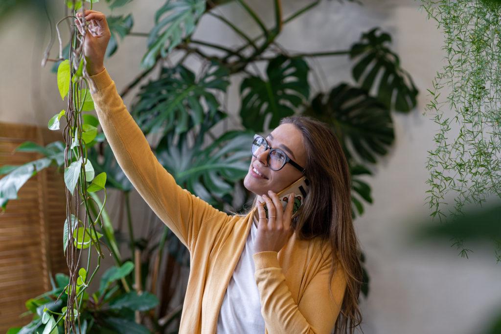 Ferienwohnung buchen, junge Frau nimmt telefonische Buchung entgegegen und pflegt dabei Wohnungspflanzen