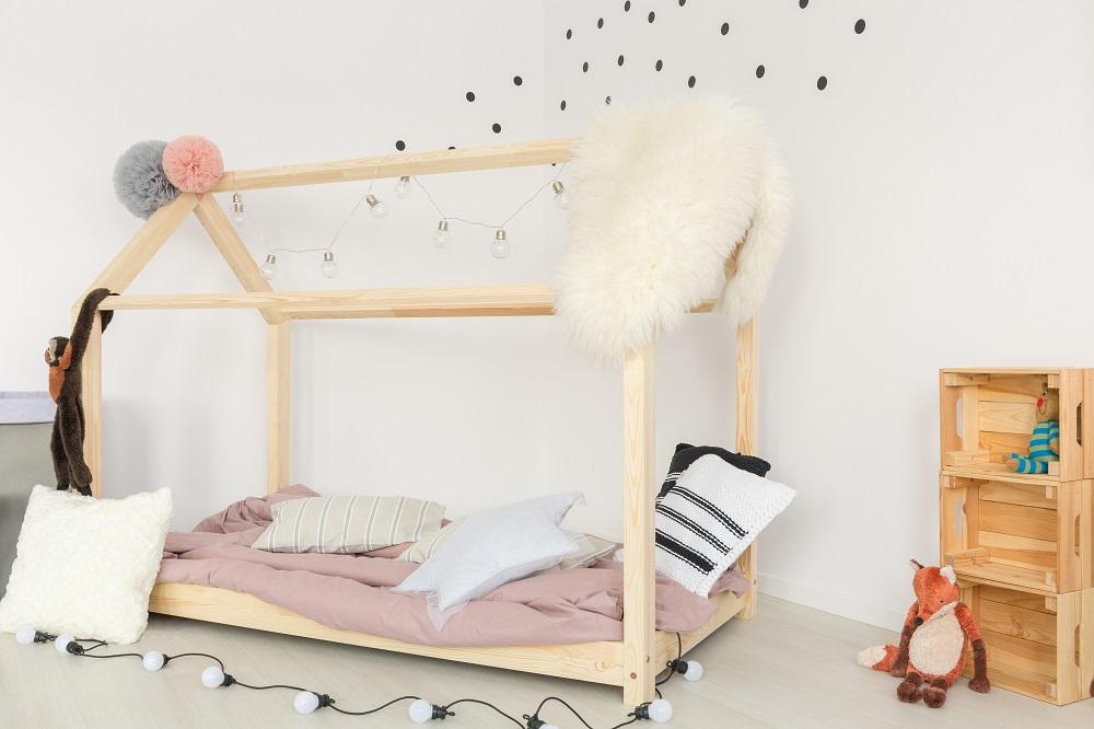 Kinderbett aus Holz vor gepunkteter Wand