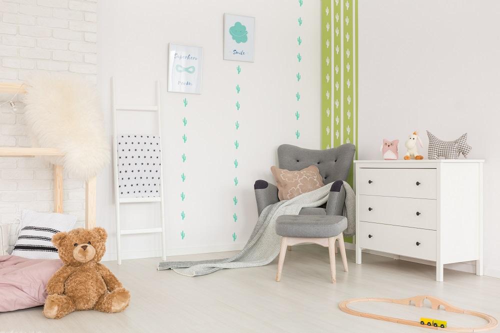 Kinderzimmer in einer Ferienwohnung mit weißer Komode, Sessel, Bildern und Teddybär