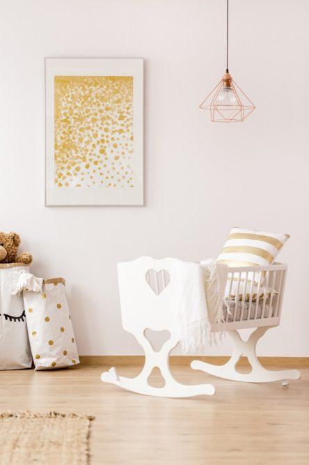 Babybett in einer Ferienwohnung im Kinderzimmer mit Bild, Lampe und Wäschesack
