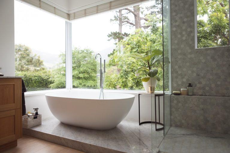 Modernes Badezimmer in einer Ferienwohnung, weißre freistehende Badewanne vor großer Fensterfront