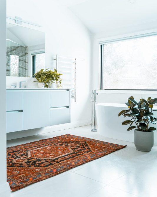 Modernes Bad in einer Ferienwohnung, weiße Fliesen und Möbel