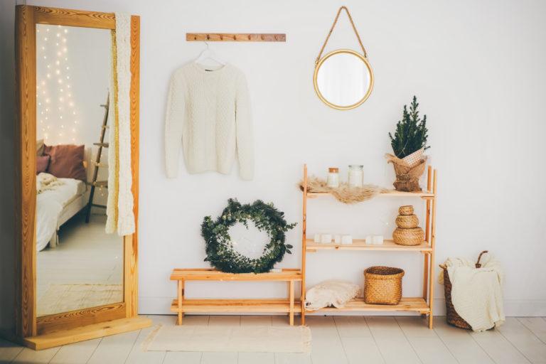 Flur einer Ferienwohnung mit Holzspiegel und Regalen