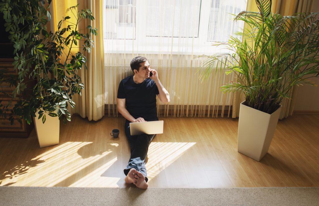 Ferienwohnungsbesitzer sitzt mit Laptop auf dem Boden und jimm Buchungen entgegen