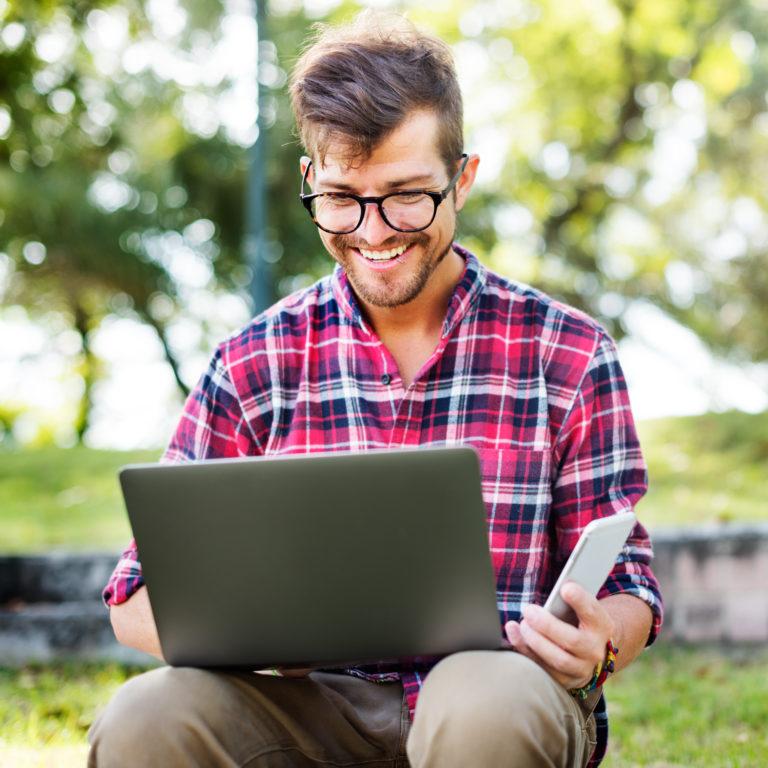 Ferienwohnung vermarkten, junger Ferienwohnungsbesitzer am Laptop