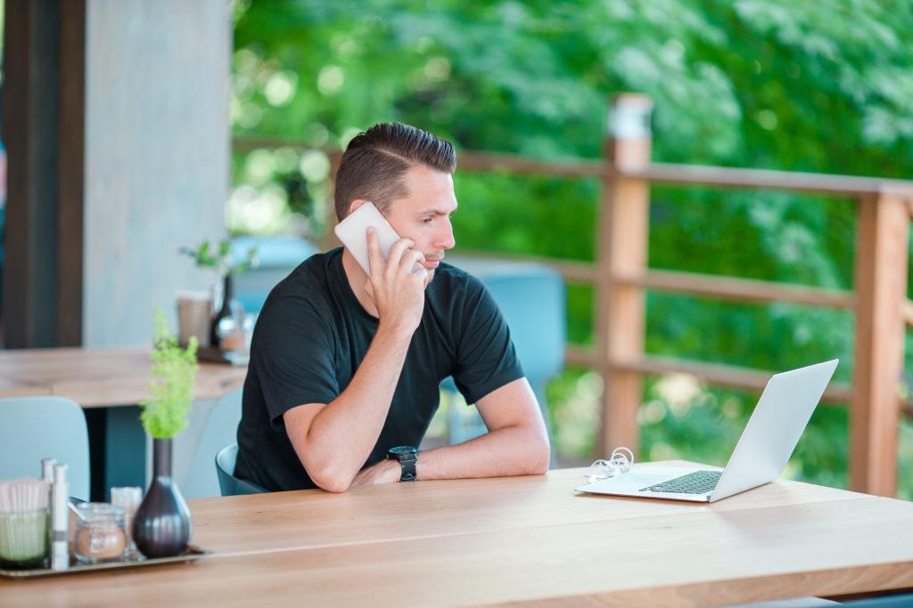 Ferienwohnung vermarkten, junger Mann nimmt Buchungen via Telefon entgegen