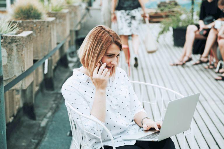 Frau vor dem Laptop nimmt Buchungen für Ferienwohnung entgegen